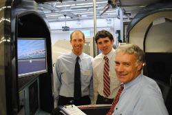 photograph - Man in a flight simulator, two others look on